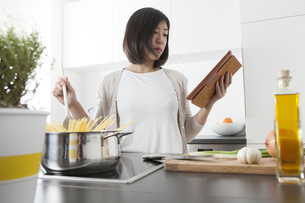 Young woman using digital tablet while cooking spaghettiの写真素材 [FYI04339413]