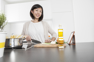 Portrait of smiling young woman cutting spring onions in theの写真素材 [FYI04339414]