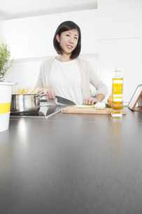 Portrait of smiling young woman cutting spring onions in theの写真素材 [FYI04339415]