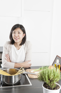 Portrait of smiling young woman cooking spaghettiの写真素材 [FYI04339416]