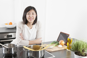 Portrait of smiling young woman cooking spaghettiの写真素材 [FYI04339419]
