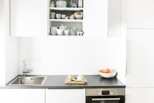 Modern kitchen, chopping board with vegetables, open cupboarの写真素材 [FYI04339420]