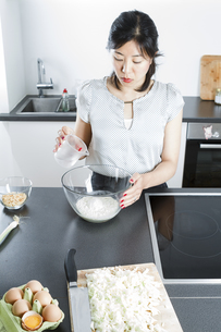 Woman pouring water in a glassbowl of flourの写真素材 [FYI04339422]