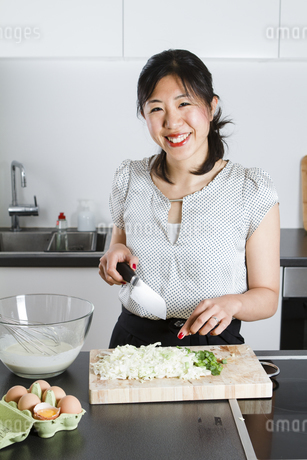 Portrait of smiling woman cutting spring onions in a kitchenの写真素材 [FYI04339427]
