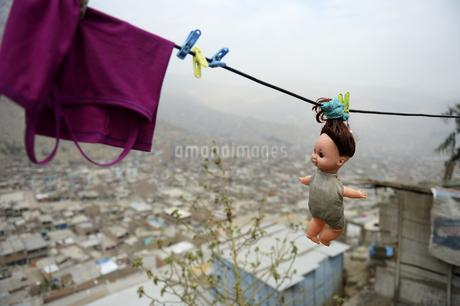 Peru, Lima, Huaycan, doll hanging on washing lineの写真素材 [FYI04339446]