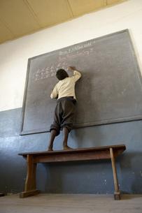 Madagascar, Fianarantsoa, Schoolboy writing on blackboardの写真素材 [FYI04339451]