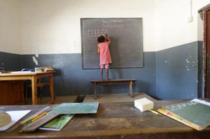 Madagascar, Fianarantsoa, Schoolgirl writing on blackboardの写真素材 [FYI04339454]
