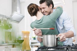 Germany, Cologne, Man preparing sauce, woman embracing manの写真素材 [FYI04339458]