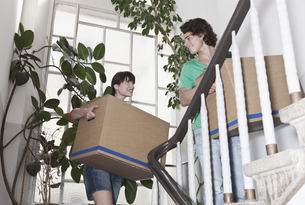 Germany, Cologne, Young couple carrying carton on stairway iの写真素材 [FYI04339463]