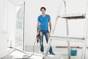 Germany, Cologne, Young man holding electric drill in renovaの写真素材 [FYI04339464]