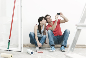 Germany, Cologne, Young couple watching cell phone picturesの写真素材 [FYI04339465]