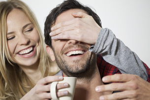 Woman covering eyes of man and holding coffee cup, smilingの写真素材 [FYI04339471]