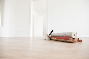 Moving house with rolls of wallpaper on wooden floorの写真素材 [FYI04339476]