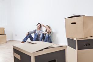 Couple sitting on floor with moving boxesの写真素材 [FYI04339481]