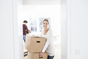Woman unloading boxes in their new house while man in backgrの写真素材 [FYI04339482]