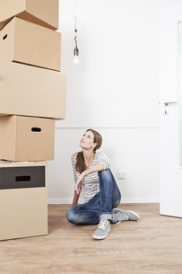 Woman sitting on floor besides stack of cardboard boxesの写真素材 [FYI04339484]