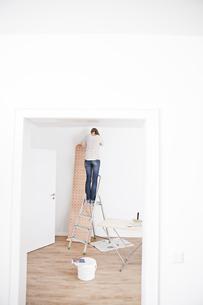 Woman sticking wallpaper on wallの写真素材 [FYI04339485]