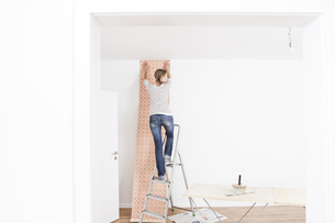 Woman sticking wallpaper on wallの写真素材 [FYI04339486]