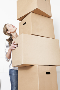 Woman carrying stack of cardboard boxes, looking upの写真素材 [FYI04339487]