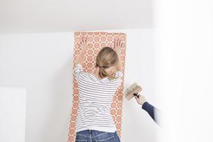 Woman sticking wallpaper on wallの写真素材 [FYI04339488]