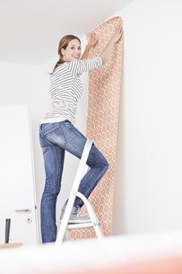 Woman sticking wallpaper on wallの写真素材 [FYI04339489]