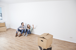 Couple sitting on floor and pointing at wallの写真素材 [FYI04339498]