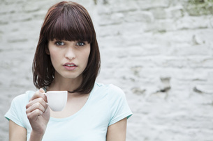 Germany, Cologne, Portrait of young woman holding coffee cupの写真素材 [FYI04339513]
