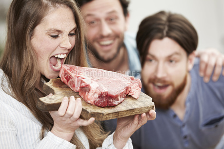 Happy young womanpretending to bite into raw steakの写真素材 [FYI04339522]