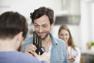 Friends in kitchen drinking beerの写真素材 [FYI04339524]