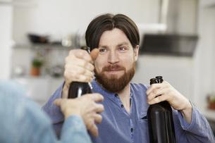 Friends in kitchen drinking beerの写真素材 [FYI04339525]