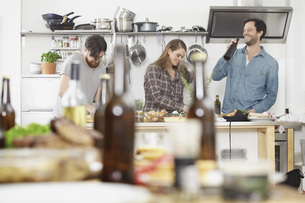 Friends preparing food in kitchenの写真素材 [FYI04339526]