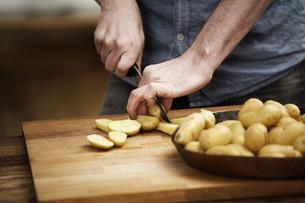 Man cutting potatoes in kitchenの写真素材 [FYI04339527]