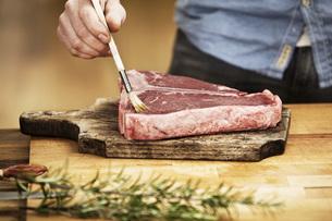 Man preparing steak in kitchenの写真素材 [FYI04339529]