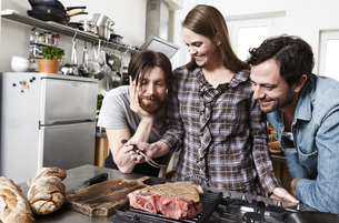 Friends preparing food in kitchenの写真素材 [FYI04339530]