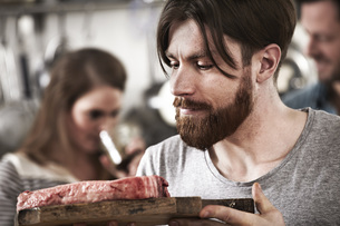 Man looking at raw steak on chopping boardの写真素材 [FYI04339531]