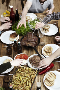 Friends eating potatoes, steaks and meatballs at wooden tablの写真素材 [FYI04339532]
