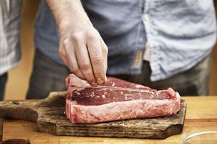 Man preparing steak in kitchenの写真素材 [FYI04339534]