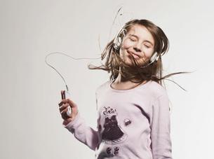 Girl (10-11) listening music, smilingの写真素材 [FYI04339539]