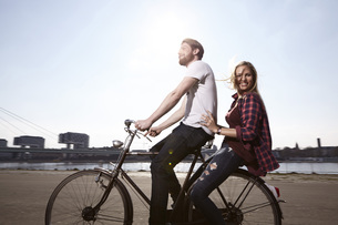 Happy couple riding bicycle on riverbankの写真素材 [FYI04339541]