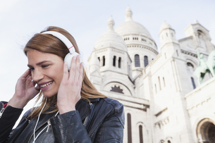 France, Paris, portrait of happy young woman listening musicの写真素材 [FYI04339556]