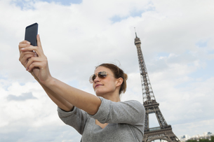 France, Paris, portrait of young woman photographing herselfの写真素材 [FYI04339564]