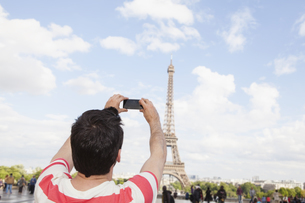 France, Paris, man photographing Eiffel Tower with his smartの写真素材 [FYI04339565]