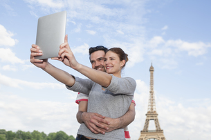 France, Paris, happy couple photographing themself with tablの写真素材 [FYI04339566]