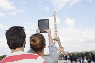 France, Paris, couple photographing  Eiffel Tower with tableの写真素材 [FYI04339567]