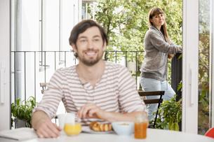 Man having breakfast with woman standing on balconyの写真素材 [FYI04339573]