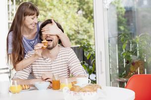 Woman feeding man at breakfast tableの写真素材 [FYI04339574]