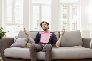 Disappointed man with pink baby shirt on couchの写真素材 [FYI04339579]