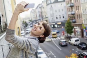 Smiling on balcony leaning back woman taking selfieの写真素材 [FYI04339585]