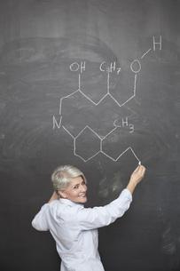 Mature teacher drawing chemical formula on blackboardの写真素材 [FYI04339590]