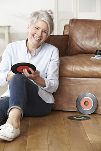 Mature woman sitting on floor holding recordの写真素材 [FYI04339594]